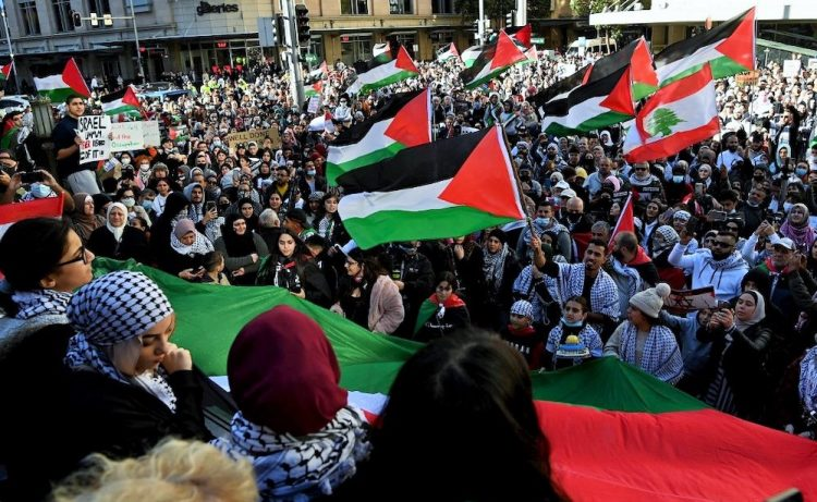 Protesters wave Palestinian flags during a demonstration against Israel at the Town Hall in Sydney on May 15, 2021, amid the ongoing conflict between Israel and the Palestinian Territories. (Photo by BIANCA DE MARCHI / AFP)
